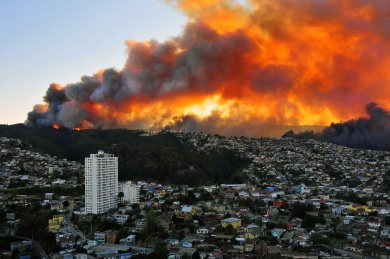 View of houses in flames during a fire in Valparaiso, 110 km west of Santiago, Chile, on April 12, 2014. Authorities decreed a red alert for the area after the fire consumed more than 100 houses. AFP PHOTO / ALBERTO MIRANDA CHILE-FIRE